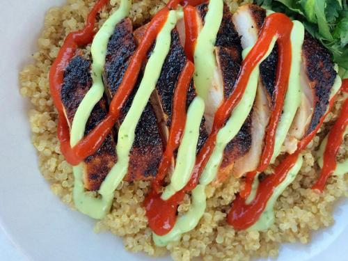 Blackened chicken with avocado-cilantro cream sauce over quinoa